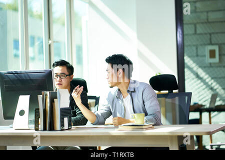 two young asian business people working together in office discussing business. - Stock Photo