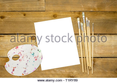 Paint brushes and dirty pallet on a rustic distressed wooden background - Stock Photo
