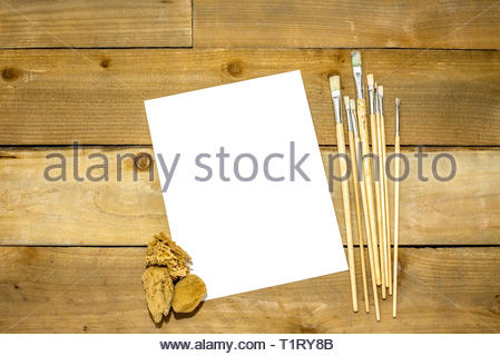 Paint brushes and sponges on a rustic distressed wooden background - Stock Photo