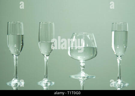 Four glasses filled with water, standing on a table, on a gray background. - Stock Photo