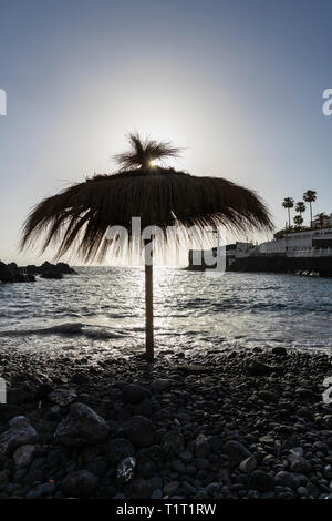Straw sun umbrella, sunshade, on the stony beach of Playa Chica, Puerto de Santiago, Tenerife, Canary Islands, Spain - Stock Photo