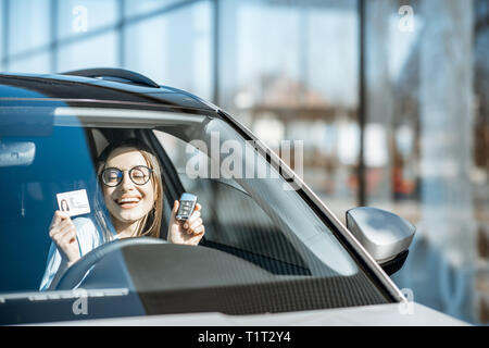 Portrait of a young woman with excited emotions holding keys and license in the new car - Stock Photo