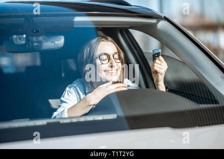 Portrait of a young woman with excited emotions holding keys in the new car - Stock Photo