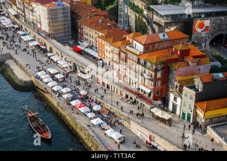 Porto, Portugal - December 2018: View from above of Cais da Ribeira, with Rabelo boat and people in the Christmas Market - Stock Photo