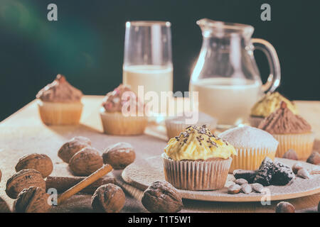 Homemade muffin cupcake with chocolate and vanilla cream on a wooden board with glass of milk in background - Image - Stock Photo