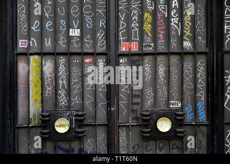 Tags and graffitis on an entrante building door - Parce de Clichy - Paris - France - Stock Photo