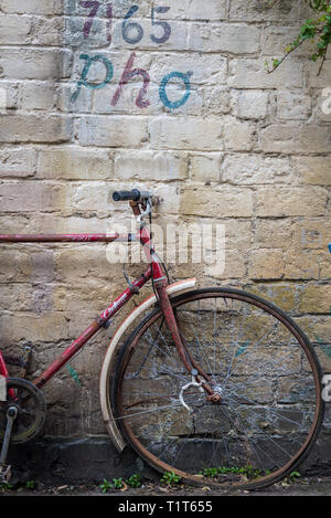 An old, rusting, abandoned red vintage bicycle in a Glasgow side street with graffiti on the wall behind it, Scotland - Stock Photo