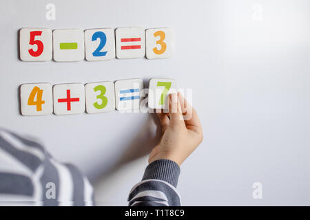The boy solves mathematical examples. A child solves examples on a blackboard. Against the background of the school board with numbers in their hands  - Stock Photo