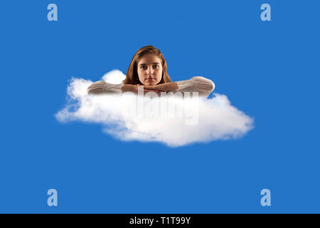 girl sitting on a fluffy white cloud against a blue clear sky - Stock Photo