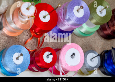 haberdashery haberdasher ribbon reels rolls rows and trims in fabric retail shop sew sewing supplies for sale retail shop market - Stock Photo