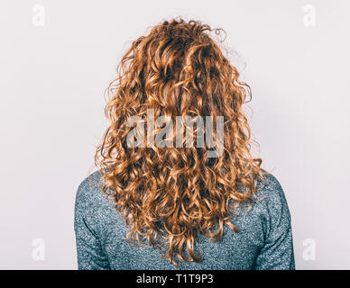 Rear view of young woman with long brown curly hair against plain background. - Stock Photo