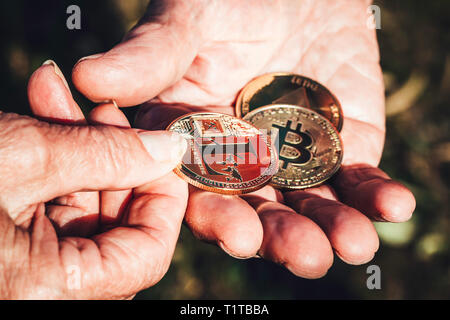 Senior woman hand is holding cryptocurrency coin in focus giving to senior man hand. Business, Finance, Investment and exchanging concepts - Stock Photo