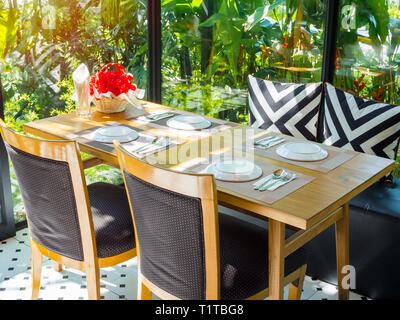 Dishware set on plate mat with bouquet red rose in basket on wooden table with chairs and pillows. Dining table set in restaurant on green nature back - Stock Photo