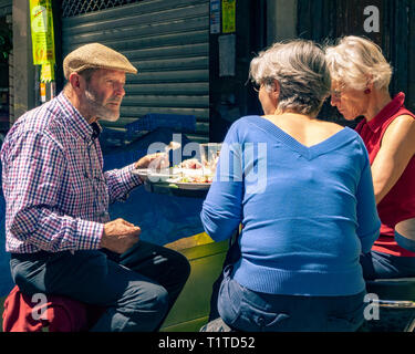 Man and two women having lunch in the Ternes market area of Paris, France - Stock Photo