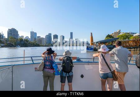 Passengers on a CityCat ferry with the city skyline behind, Brisbane River, Brisbane, Queensland, Australia - Stock Photo