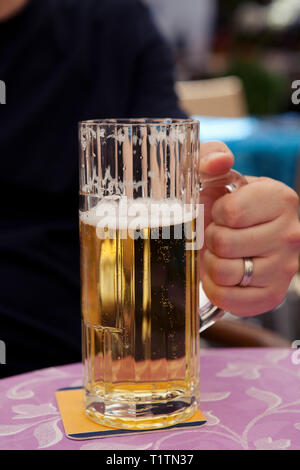 Man holding glass tankard of German beer on a table at a street cafe - Stock Photo