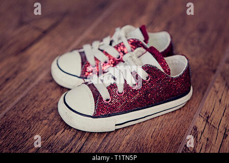 Small red baby sneakers with shoelaces on a wooden floor - Stock Photo