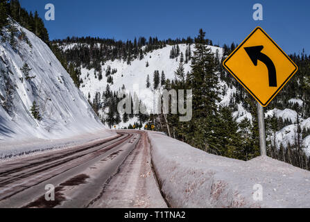 Left Curve Sign:  Motorists are warned of a sharp turn ahead on a snowy mountain road in Montana. - Stock Photo