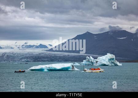 Tourists wearing life jackets taking a boat tour on amphibious vehicle passing iceberg at the Jokulsarlon glacier lake, a popular travel dastination a - Stock Photo