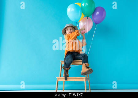 cute kid in jeans and orange shirt sitting on stairs and pointing with finger at balloons