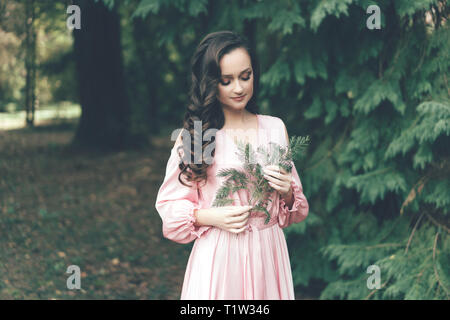femininity, pleasant girl in a pink gentle dress in the park on a warm spring day holding a twig of a coniferous tree cypress - Stock Photo
