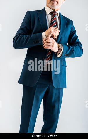 cropped view of mature businessman touching suit while standing isolated on grey - Stock Photo