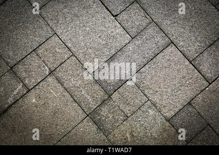 The sidewalk road made of natural stone is lined with mosaics of light gray color .Texture.Background.