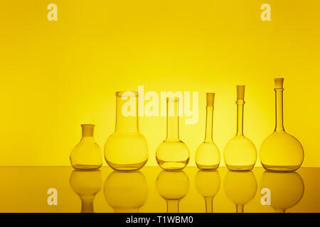 many of the beakers are in a row in the backlight, the reflection, the yellow background - Stock Photo