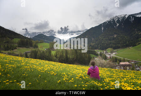 Active young woman-tourist with looking to the Santa Maddalena village in Dolomites. Forested mountains surrounded by green Alpine meadows. The concep - Stock Photo