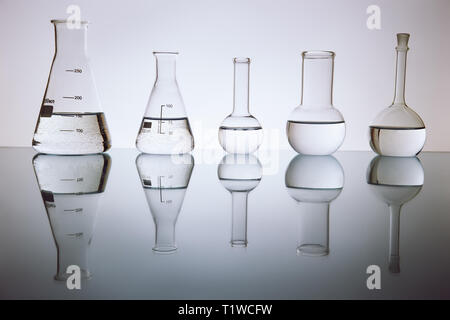 many of the beakers are in a row in the backlight, the reflection, the blue background. with liquid, - Stock Photo