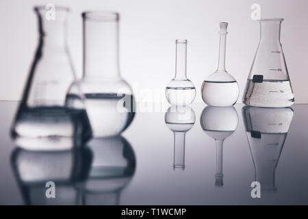 many beakers are in row, with liquid, in backlight, reflection, blue background - Stock Photo