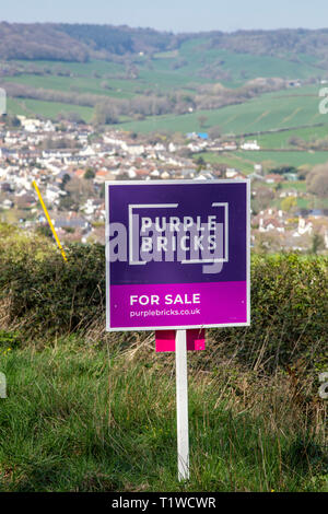Purple Bricks house for sale sign in open countryside above the village of Sidford, nr Sidmouth, Devon, UK - Stock Photo