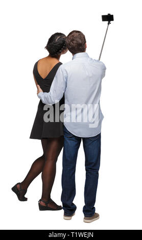 Back view of an interracial couple that makes selfie on selfie stick. beautiful friendly girl and guy together. Rear view people collection.  backside - Stock Photo