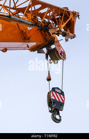A orange crane boom with hooks on a blue sky background with clipping paths - Stock Photo