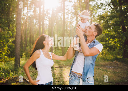 stylish young Family mom, dad and daughter one year old blonde sitting with father on shoulders playing happy and smiling, outdoors outside the city - Stock Photo