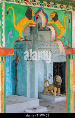 A variety of Hindu deities are carved and colorfully painted on the outside of a Hindu temple of worship in rural India - Stock Photo