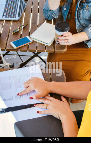Top view of two females having a business meeting at a coffee shop on a sunny day - Stock Photo