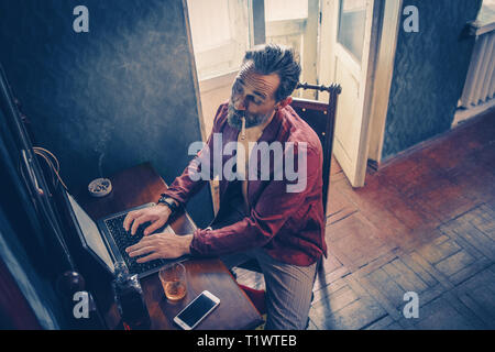 Handsome man works on his laptop smoking and drinking - Stock Photo