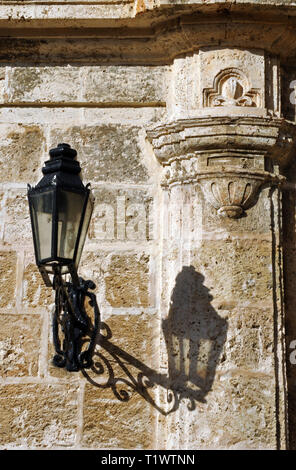 An ornate light casts a shadow on a historic stone building in Plaza de la Catedral in Old Havana, Cuba. The square is a popular tourist destination. - Stock Photo