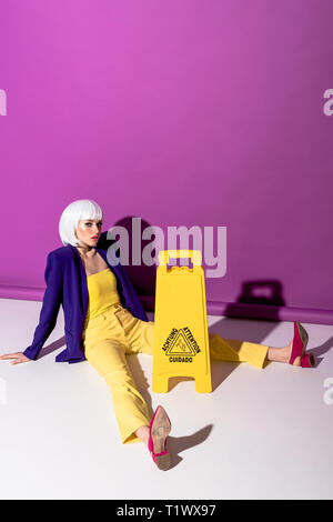 Girl in red shoes sitting near wet floor sign on purple background - Stock Photo