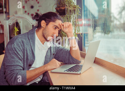 Frustrated businessman sitting on desk with hand on head looking worried at laptop. Portrait of a handsome guy wearing formal  clothing sitting near w