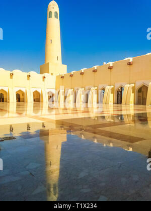 Doha, Qatar - February 21, 2019: courtyard with minaret and domes reflecting in a sunny day. Imam Abdul Wahhab Mosque or Qatar State Mosque in Middle - Stock Photo