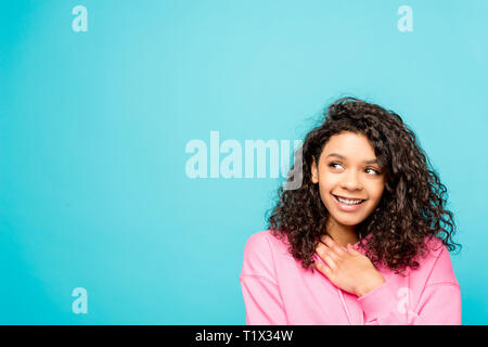 dreamy pretty african american girl smiling isolated on blue - Stock Photo