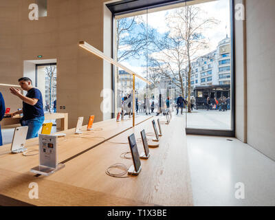 Paris, France - Mar 19 2019: Apple iPhone XS smartphones products are displayed inside the new Apple Store Champs-Elysees with people admiring burnt kiosk outside after yellow vests protest - Stock Photo