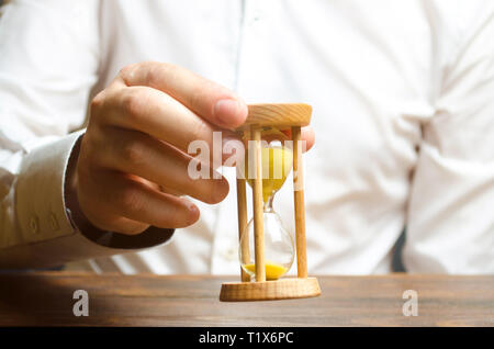 Hourglass in the hands of a person in a white shirt. Business management. Time management Increase efficiency, reduce costs and bureaucracy. Logistics - Stock Photo