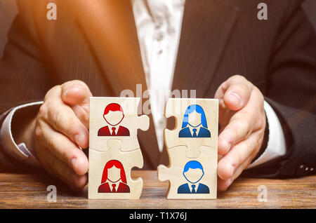 Businessman collects puzzles symbolizing the team of employees. Combining teams and people to perform work. The combination and selection of personnel - Stock Photo