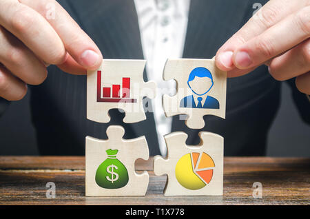A businessman collects puzzles symbolizing individual elements and attributes of doing business. Organization of the process, the creation of a busine - Stock Photo
