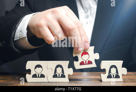 A businessman collects puzzles symbolizing a team of employees. The concept of creating a business team to perform tasks. Management and leadership sk - Stock Photo