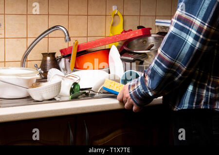Hand guy with a washcloth near a lot of dirty dishes lying in the sink in the kitchen that you want to wash. - Stock Photo