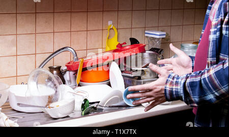 Shocked Hand guy near a lot of dirty dishes lying in the sink in the kitchen that you want to wash. - Stock Photo